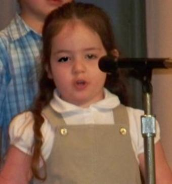 Performing on stage at my preschool graduation.